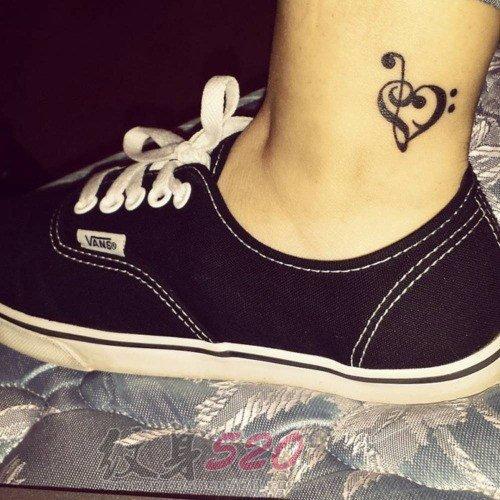 女生小腿上黑色线条心形元素音符纹身图片