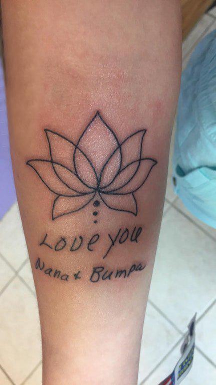 女生小腿上黑色简单线条英文和植物莲花纹身图片