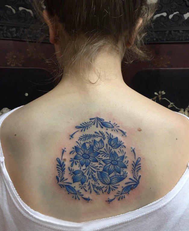 后背纹身女 女生后背上蓝色的花朵纹身图片