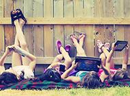 躺在草地上玩iPad的儿童ppt背景图片