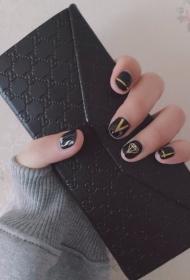 简单大方的黑色搭配金银线和个性图案美甲款式图片