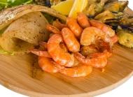 放在菜板上的美味虾与贝壳