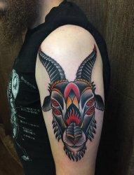 男子左手大臂上的传统风格四眼山羊头纹身图片
