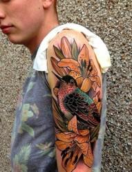 帅哥大臂上一张漂亮的百合花鸟纹身图案