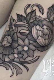 女生大腿上黑色点刺简单线条植物花朵纹身图片