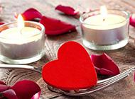 红玫瑰花瓣与点亮的蜡烛图片