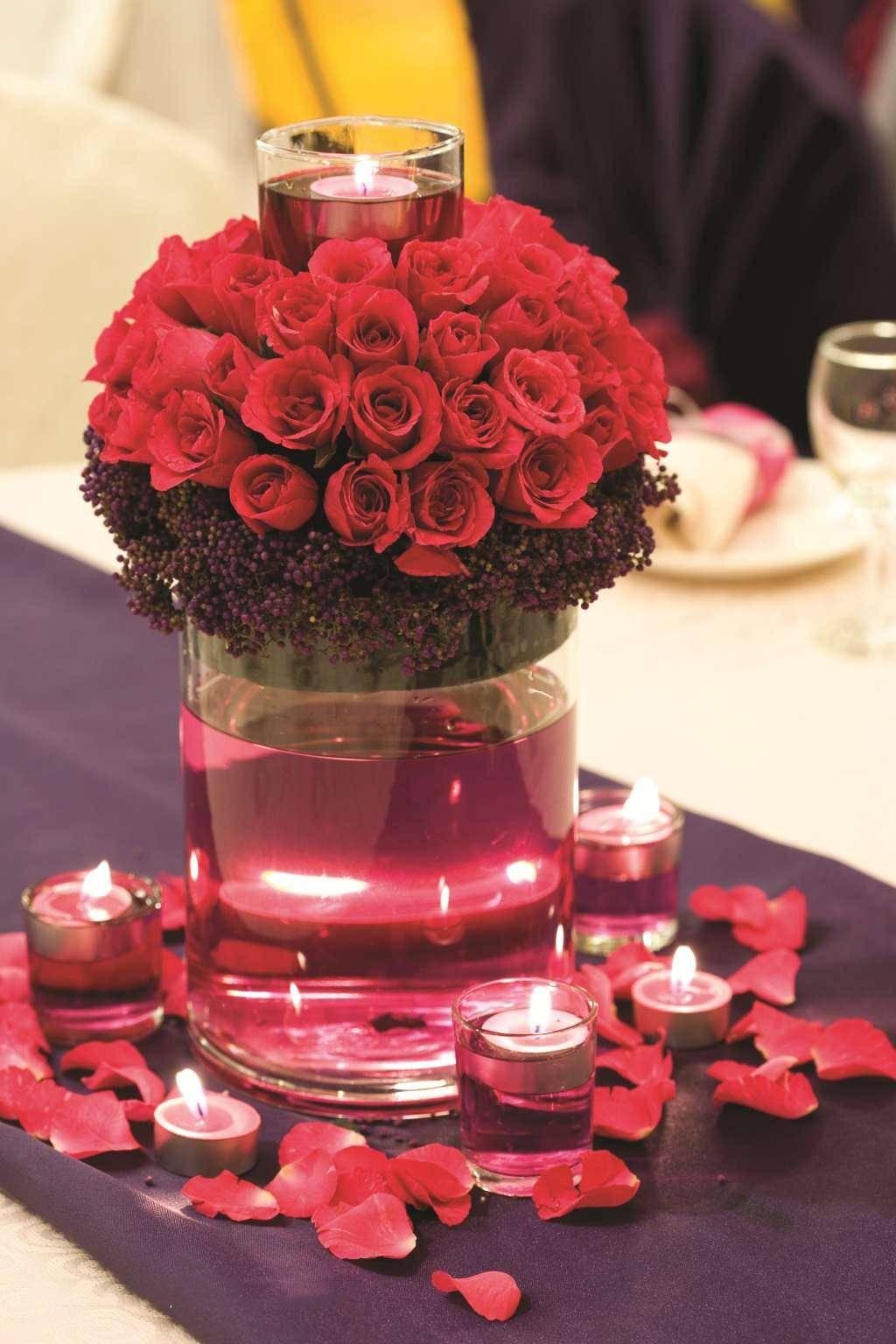 花瓶里的红玫瑰花束和蜡烛高清图片
