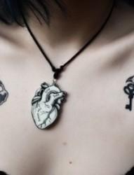 女性胸前两只燕子刺青