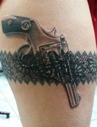 女性大腿性感的吊袜带和手枪纹身图片
