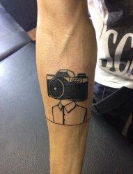 男性右手臂上黑色相机头和人身纹身图片