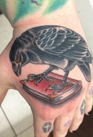 手背彩色卡通乌鸦与书纹身图案