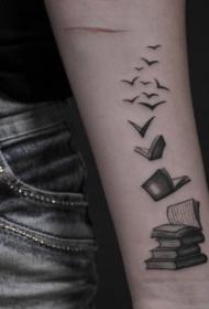 手臂苍白的书籍与成群的小鸟纹身图案