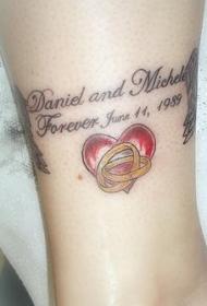 腿部彩色结婚戒指和红色的心纹身