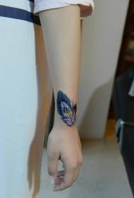 女生手腕上个性十足的彩色羽毛纹身图案