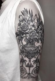 女生手臂上黑色点刺植物花瓶和花朵纹身图片